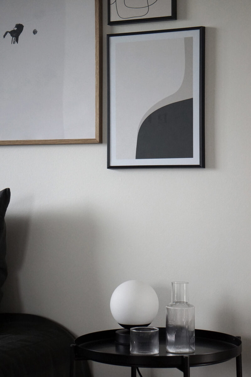 A white wall with a black thin frame hanging on the wall with an art print inside with the title Right Here 02