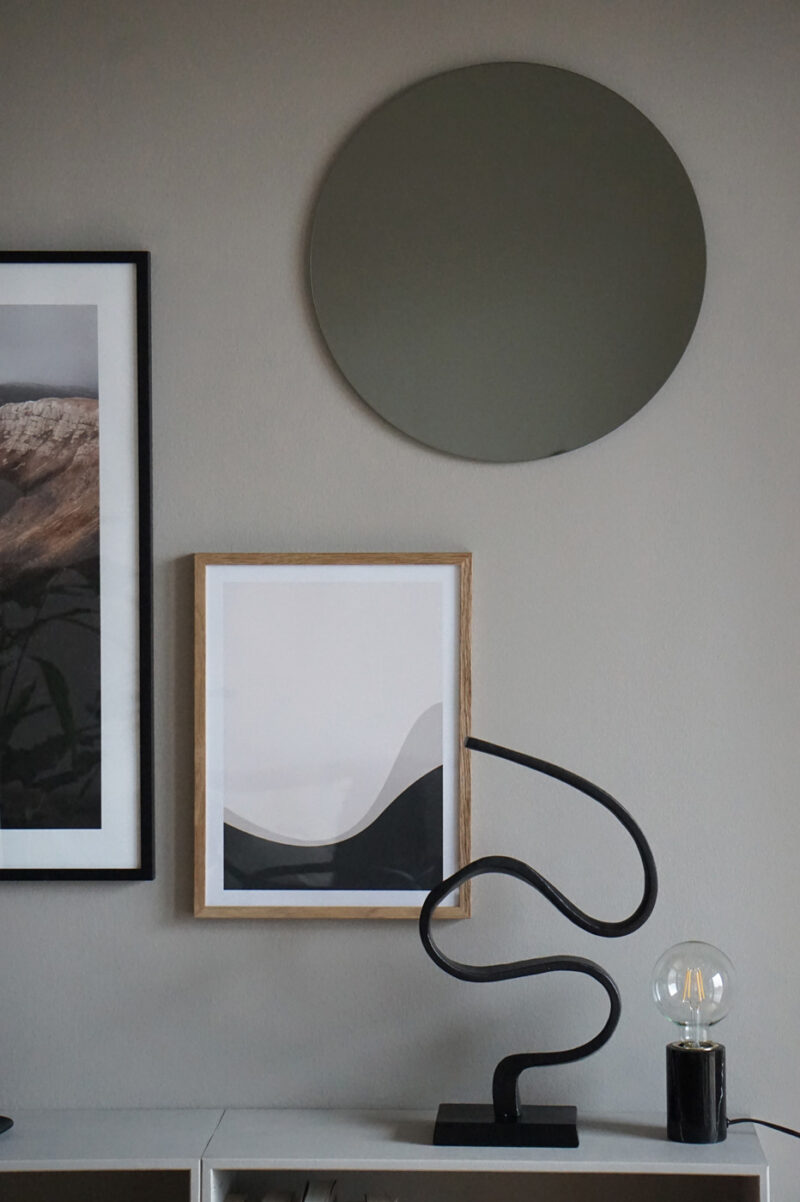 A light brown wall with an oak frame with the art print; Right Here 04 inside. A black minimal sculpture is partly in front of the frame.