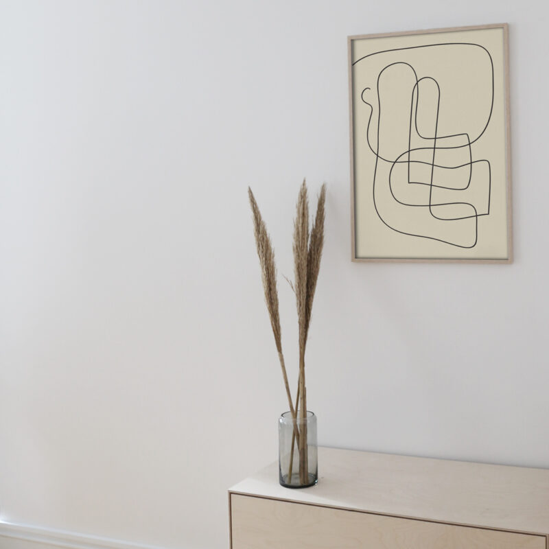 The Pen 04 art print inside a thin oak frame hanging on a white wall