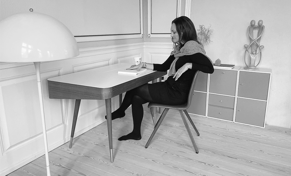 black/white photo with woman sitting on a chair at a work table