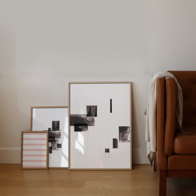 three oak frames standing on the floor with the Selected Blacks series of art prints