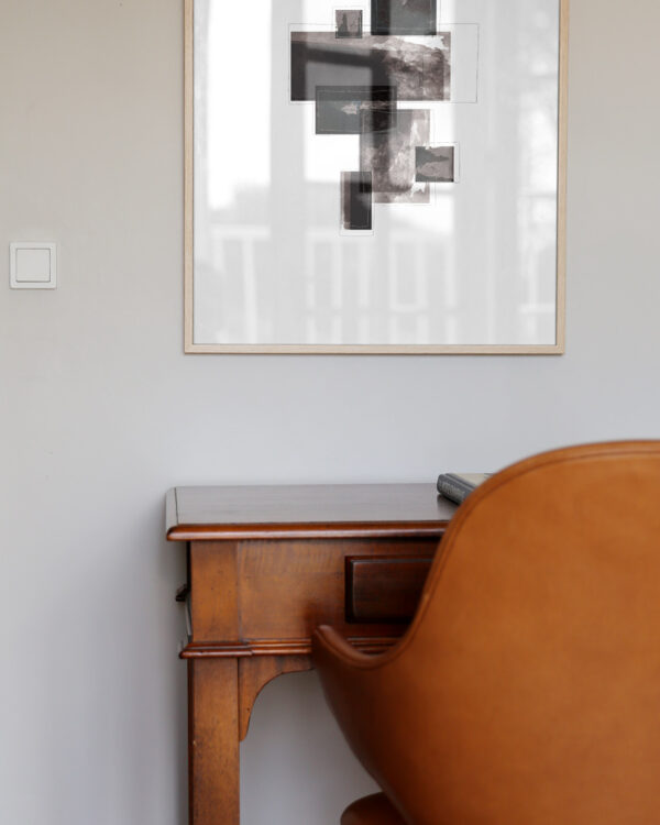 oak frame hanging on wall with an minimal art print inside