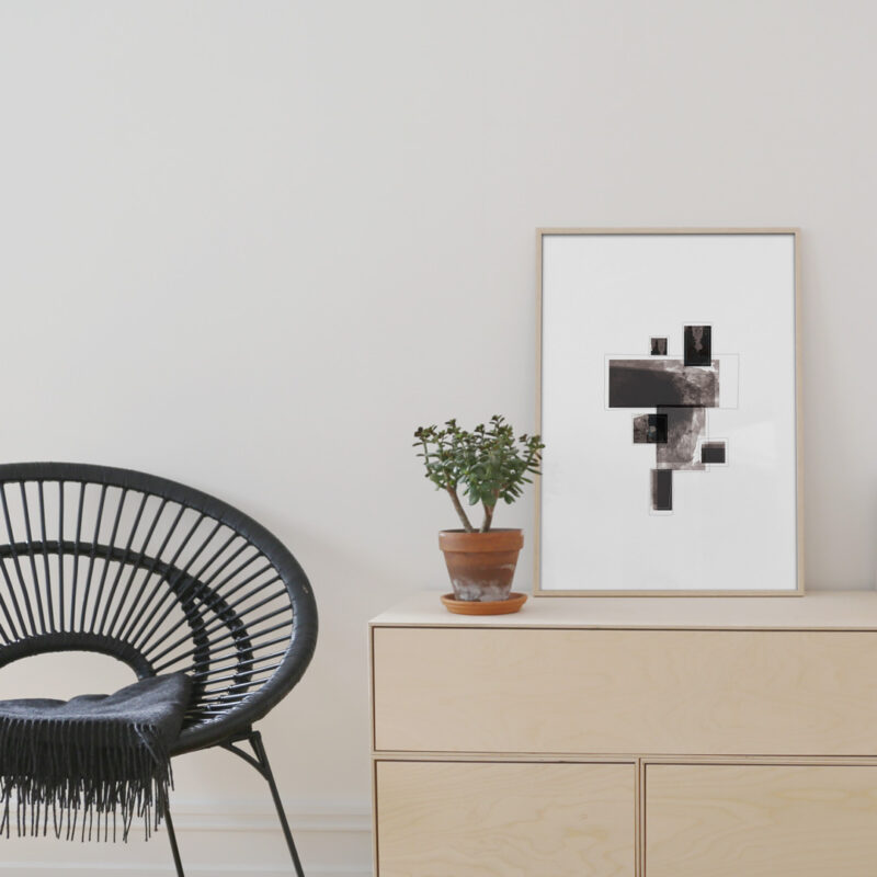 oak frame with black minimal art print standing on furniture next to a black chair