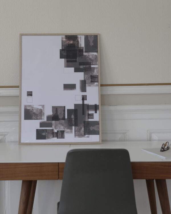 a work table with a thin oak frame standing on it with an art print inside with the title Selected Blacks 06
