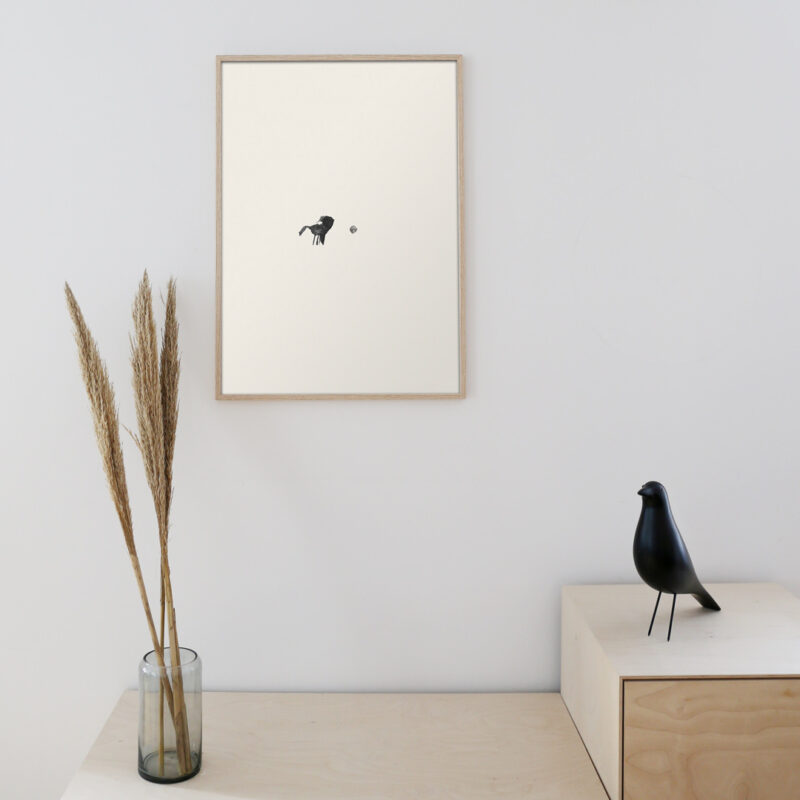 art print hanging on the wall in a oak frame in front a black eames design bird created in wood
