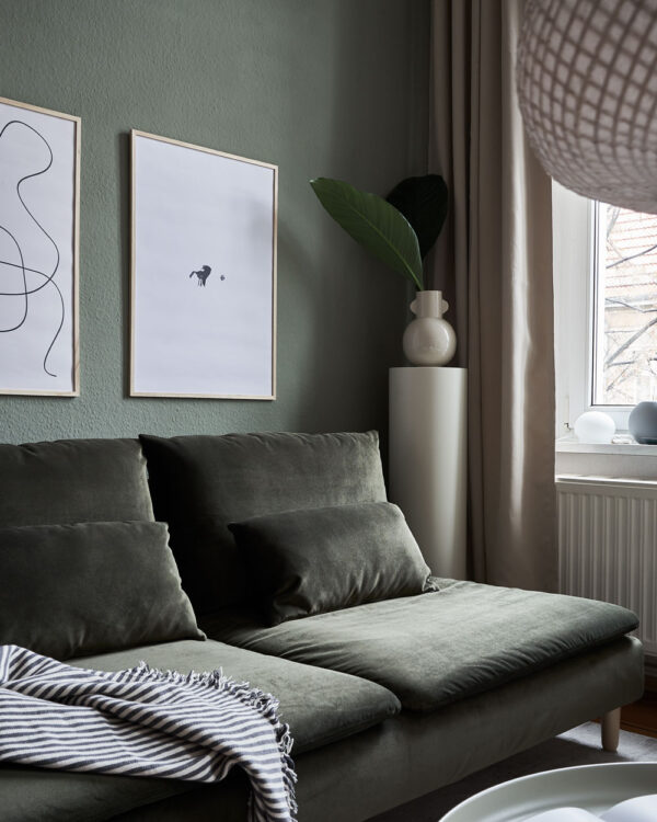 a living room with dark green walls and couch with two art prints on the wall with the title; The Pen 02 and The Dot