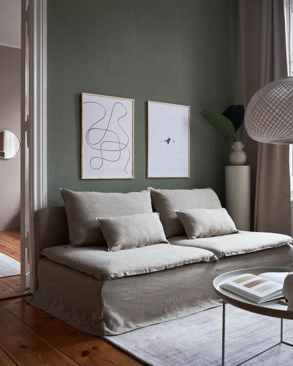 a living room with dark green walls and a beige couch with two art prints on the wall with the title; The Pen 02 and The Dot