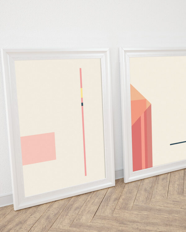 two white frames standing on wooden floor with art prints inside in coral and orange colors