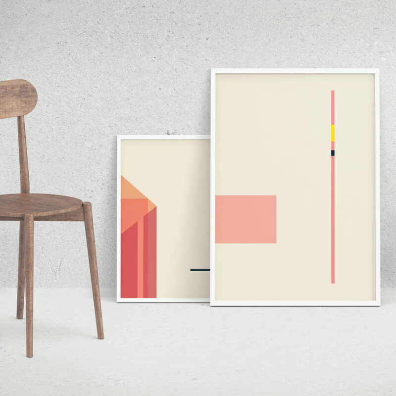 Two white frames with the art print Coral Objects 08 inside, standing on the floor next to a chair