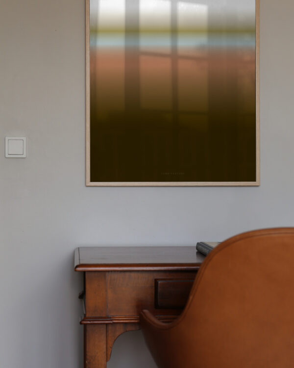 An oak frame with the art print inside called; Dusk 01, hanging on a white wall with a work table and chair below.