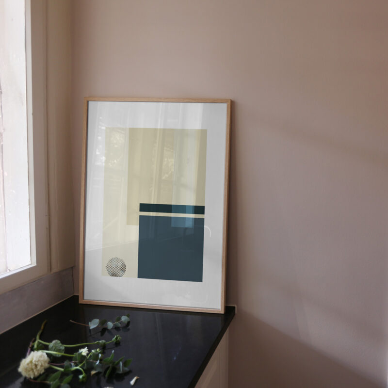 An oak frame with an art print inside with the title; Blue Notes 01, standing on the kitchen table up against a dusty pink wall
