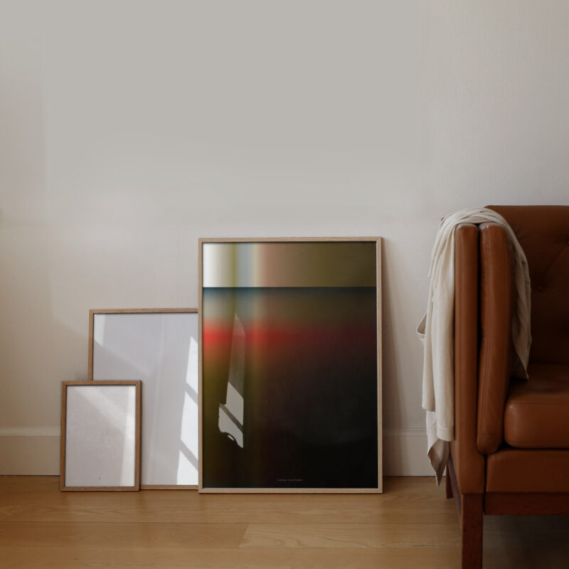 The art print with the title; Dusk 02 in an oak frame standing on the floor next to lether couch