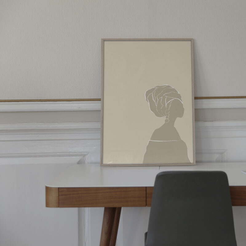Frey art print is the title of this artwork in a thin oak frame, standing on a work table with a dark grey chair in front